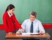 Schoolgirl Asking Question To Teacher At Desk — Stock Photo