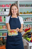 Saleswoman Holding Vegetable Packet In Grocery Store — Stock Photo
