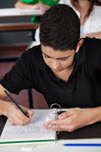 Student Copying From Cheat Sheet At Desk — Stock Photo