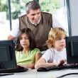 Teacher Looking At Schoolchildren Using Desktop Pc — Stock Photo