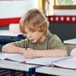 Schoolboy Writing On Book In Classroom — Stock Photo