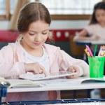 Schoolgirl Using Digital Tablet In Classroom — Stock Photo #28578807