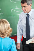 Teacher With Duster And Chalk Looking At Boy — Foto Stock