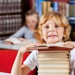 Schoolboy With Stack Of Books Sitting In Library — Stock Photo #28597147