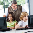 Teacher Looking At Schoolchildren Using Desktop Pc — Stock Photo #28597267