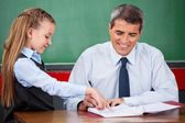 Little Girl Asking Question To Male Teacher At Desk — Stock Photo