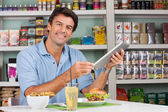 Male Customer With Digital Tablet And Snacks At Table — Стоковое фото