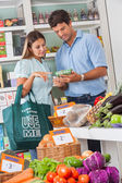 Couple Reading Product Details In Supermarket — Stock Photo