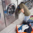 Stock Photo: Man Searching Clothes Inside Washing Machine