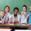 Schoolchildren Gesturing Thumbs Up With Teacher At Desk — Stock Photo