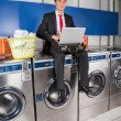 Businessman With Laptop In Laundry — Stock Photo #28999241