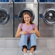 Woman Sitting Against Washing Machines At Laundry — Stock Photo