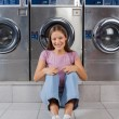 Stock Photo: Woman Sitting Against Washing Machines At Laundry
