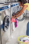 Woman Loading Washing Machine With clothes — Stok fotoğraf