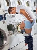 Man Undressing His Clothes In Front Of Washing Machine — Stock Photo