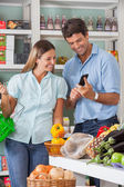 Couple Using Mobilephone While Shopping In Supermarket — Stock Photo