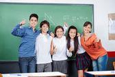 10 代の学生が一緒に親指を身振りで示す — ストック写真