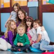 Teacher And Students Sitting Together On Floor — Stock Photo #29014339