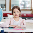 Schoolgirl Sitting At Desk With Globe And Stack Of Books — Stock Photo #29018993