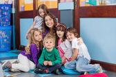 Insegnante e studenti seduti insieme sul pavimento — Foto Stock