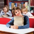 Cute Schoolboy Sitting With On Stack Of Books At Table In Librar — Stock Photo #29132817