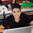 Happy Teenage Schoolboy Sitting With Laptop In Classroom — Stock Photo #29134767