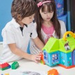 Stock Photo: Boy And Girl Playing With Plastic House In Kindergarten