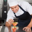 Stock Photo: Young Chef Decorating Delicious Dessert