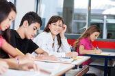 Adolescente con amigos en el escritorio de la escritura — Foto de Stock
