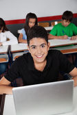 Happy Teenage Schoolboy Sitting With Laptop In Classroom — Stock Photo