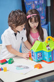 Boy And Girl Playing With Plastic House In Kindergarten — Stock Photo