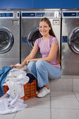 Woman With Laundry Basket Sitting In Front Of Washing Machine — Stock Photo