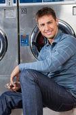 Man Listening To Music At Laundromat — Stock Photo