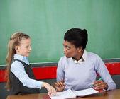 Kız öğrenci ve öğretmen masa başında birbirine bakarak — Stok fotoğraf
