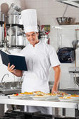 Chef With Checklist And Pasta Dishes At Counter — Stock Photo