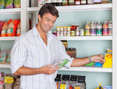 Man Selecting Food Packets In Store — Stock Photo