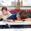 图库照片: Boy Sleeping On Desk In Classroom