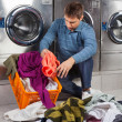 MPutting Dirty Clothes In Basket at Laundromat — Stock Photo #29335511