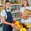 Stock Photo: SaleswomHolding Vegetable Basket With Female Customer