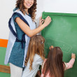 Teacher And Children Writing On Chalkboard In Classroom — Stock Photo