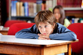 Bored Schoolboy Looking Away While Leaning On Table — Stock Photo