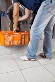 Muž s košíkem uvedení oblečení do pračky — Stock fotografie