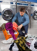 Man Putting Dirty Clothes In Basket at Laundromat — Stock Photo