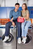 Casal que estava em máquinas de lavar roupa — Fotografia Stock