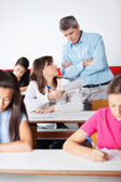 Angry Teacher Looking At Student During Examination — Stock Photo