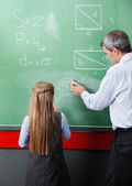 Girl Standing With Teacher Wiping Board In Classroom — Stock Photo