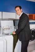 Businessman Washing Clothes At Laundromat — Stock Photo