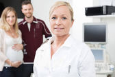Obstetrician With Expectant Couple In Background — Stock Photo