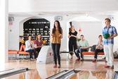 Gelukkige vrouw met vrienden in bowlingclub — Stockfoto