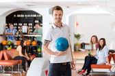 Jonge man houden blauwe bowling bal in club — Stockfoto